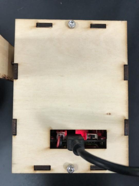 柵欄中的 Mbitbot mini 充電時亮起紅色的指示燈